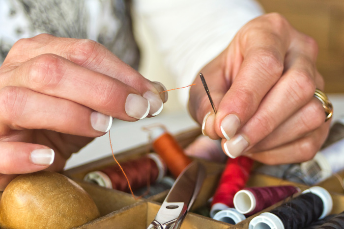Spraying a little bit of hairspray on the end of thread can help to pull it through the needle.