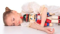 A young ballerina dreams of far away lands with The Nutcracker in her arms - Getty Images