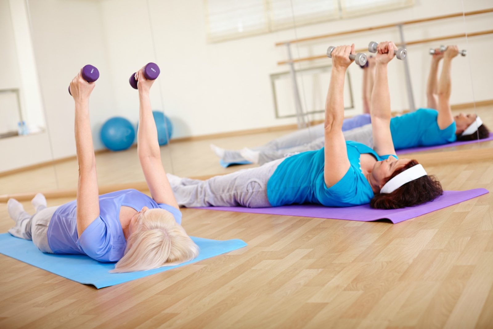 Older women doing dumbbell floor exercises