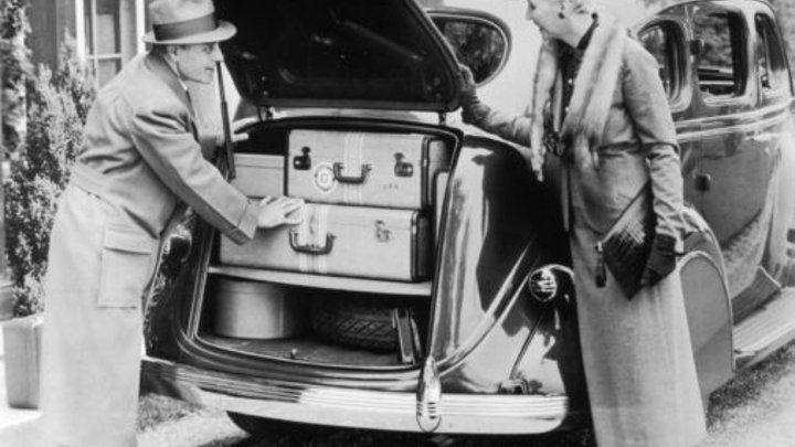 A mature couple pack the trunk of their Chrysler Royal Sedan, 1936.  Source: Getty